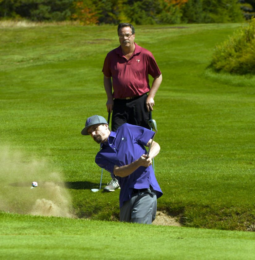 Larry Pickreign Jr. escapes from a bunker while his dad Larry watches from behind during Tuesday's 39th annual Bar Fly Open golf tournament.  (Enterprise photo — Lou Reuter)
