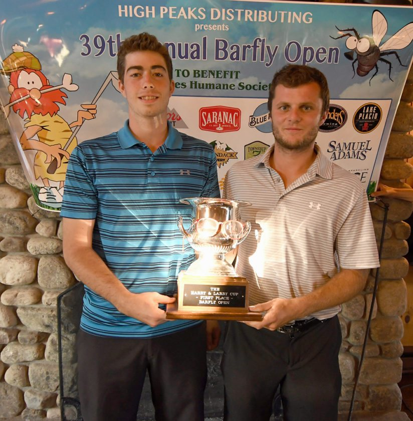 Mike Rice, left, and Devin Darrah hold the Harry and Larry Cup as champions of the 39th annual Bar Fly Open golf tournament held Tuesday at the Lake Placid Resort's Links Course. The pair finished with a 9-under par. (Enterprise photo — Lou Reuter)