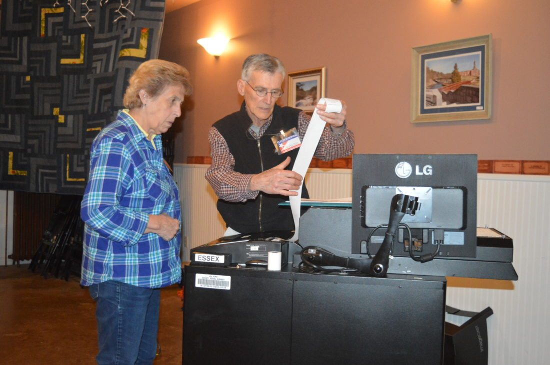 Election inspectors Lorraine Vincent and Dean Melville look at the results from the polling center at Amos and Julia Ward Theater at 12 Parkside Road in Jay shortly after polls closed at 9 p.m. Tuesday. (Enterprise photo — Antonio Olivero)