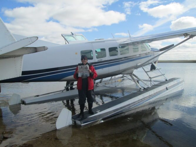 Mary Brown holds a copy of the Enterprise on a bush plane during her recent canoe trip on the Thelon River, Northwest Territories, Canada.   (Photo provided)