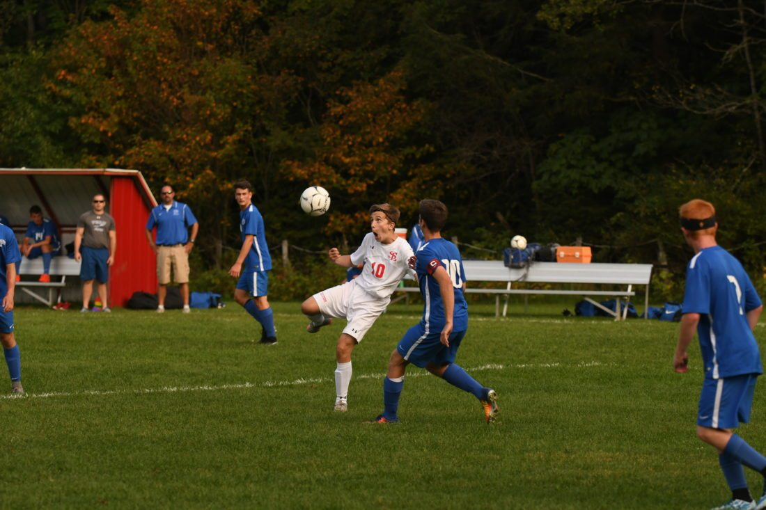 Saranac Lake's Owen Yando winds up for a shot while LJ Nuzzo closes in on defense during Wednesday's game at Schroeter's Field. (Enterprise photo — Lou Reuter)