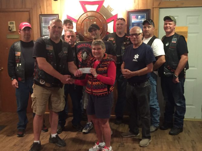 The Franklin County chapter of the Warthogs motorcycle club donated $2,000 to High Peaks Hospice on Aug. 28 at the Veterans of Foreign Wars post in Tupper Lake. At front is Warthogs member Erik Hall presenting Marie VanNortwick of Hospice with a check. Pictured behind them from left, are Brian Gary, Shawn Landry, Barry Hall (VFW member), Justin Blinn, Chris Segard, Phil Smith (VFW member), Mike Sisto and Jon Boyea. Not pictured is Warthogs member Mark Staves. The Warthogs thanks the following businesses and organizations for their help with this fundraiser: Tupper Lake VFW Post 3130, Foul Line Sports Bar, NYSCOBPA, ORDA, Tupper Lake Golf Club, Holbert's Supply, Evergreen Auto Center, Adirondack Auto Parts, Serendipity, Adirondack Wine & Spirits, Jrecks in Malone and Lake City Choppers. (Photo provided)