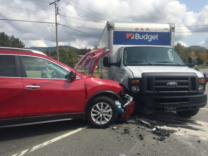 The Saranac Lake Volunteer Rescue Squad transported one person with minor injuries to Adirondack Medical Center in Saranac Lake Friday as a 2017 Nissan Rogue collided with a 2014 Budget moving truck in front of the state police Troop B headquarters on state Route 86 in Ray Brook, a Saranac Lake Volunteer Fire Department member said. The collision took place shortly before noon. (Enterprise photo — Brittany Proulx)