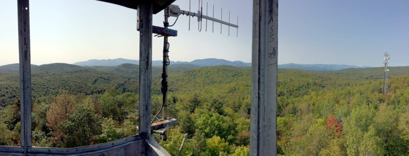 The High Peaks can be seen from the fire tower cabin on Belfry Mountain, which is one of four hikes that make up the Moriah Challenge. (Enterprise photo — Justin A. Levine)