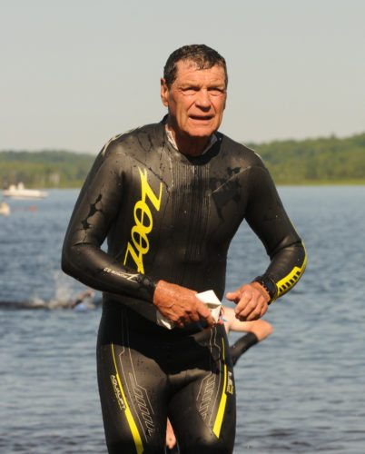Bob Tebo finishes off his swim leg in his hometown during the 2016 Tupper Lake Tinman Triathlon. A week ago, Tebo took first place in his age group at the Ironman 70.3 World Championships in Chattanooga, Tennessee. (Enterprise file photo — Lou Reuter)