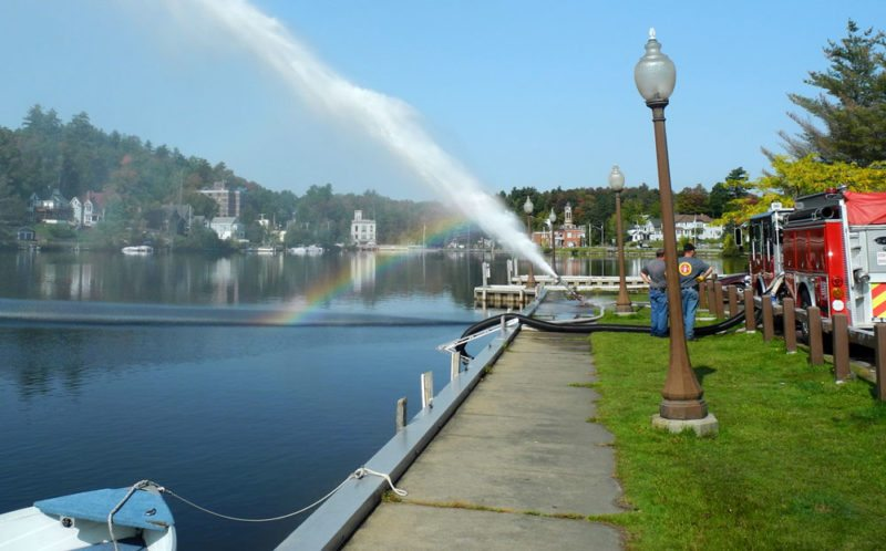 A rainbow appears as the Saranac Lake Volunteer Fire Department tests the pumps on engines 143 and 145 by shooting water at 15,000 gallons a minute over Lake Flower. The annual test ensures the pumps are up to the National Fire Protection Association's regulations. (Enterprise photo — Aaron Cerbone)