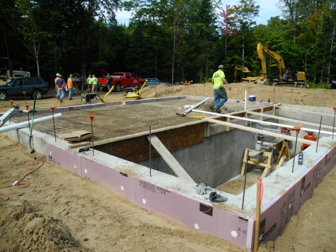 A Danko Construction worker walks over the foundation of the well's future pump house, which will bring water 3 miles down Kildare Road to connect with the existing water system in Tupper Lake. (Enterprise photo — Aaron Cerbone)