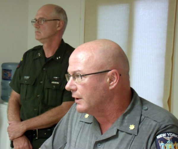 Maj. John Tibbits, front, commander of New York State Police Troop B, and Eric Lahr, division director of the state forest ranger program, speak Monday afternoon in Newcomb about finding the body of Alex Stevens, 28, in the High Peaks Wilderness. (Photo provided — Brian Mann, North Country Public Radio)