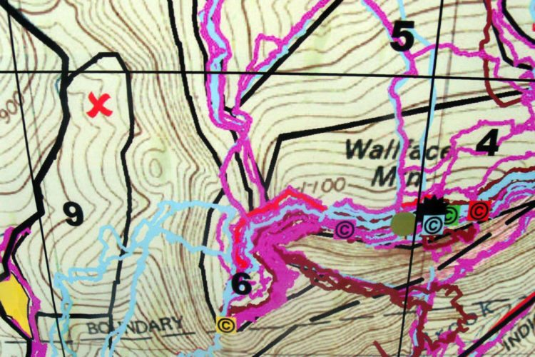 "A search map shows where Alex Stevens was found, marked with a red X, as well as colored circles with ""c""s marking ""clues"" he left behind, as seen Monday at a press conference in Newcomb. Search officials did not talk about these clues. (Photo provided — Brian Mann, North Country Public Radio)"