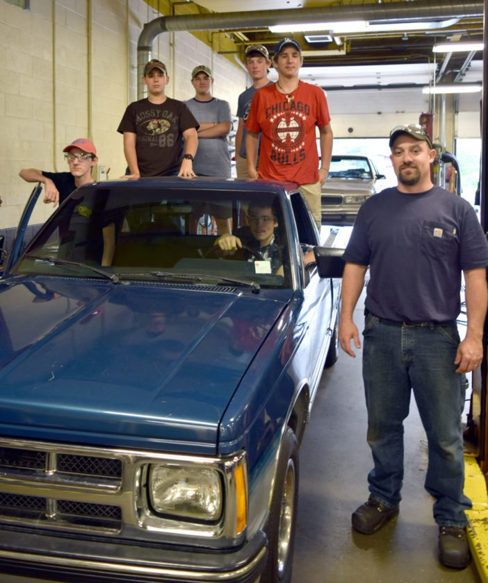 Zach Fredenburg, far right, and the students of the Auto Tech class, which will gain space to work on hybrid and electric vehicles if the capital project is approved. Students pictured: Bradley Russ (Saranac Lake), Jeremiah Bell (Tupper Lake), Ray Amell (Saranac Lake), Will Holmlund (Saranac Lake), Eddie Sovey (Saranac Lake) and Dillon Fezette (Saranac Lake).  (Enterprise photo —  Glynis Hart)