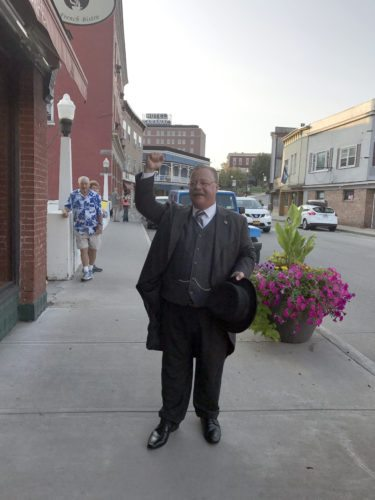 Theodore Roosevelt impersonator Joe Wiegand poses on Broadway in downtown Saranac Lake this morning. He will perform a free show at 7  tonight at the Harrietstown Town Hall, 39 Main St. (Enterprise photo — Catherine Moore)