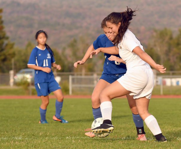 Lake Placid's Natalie Tavares and Seton Catholic's Sydney Falb battle for possession during Wednesday's match at the North Elba athletic fields in Lake Placid. (Enterprise photo — Lou Reuter)
