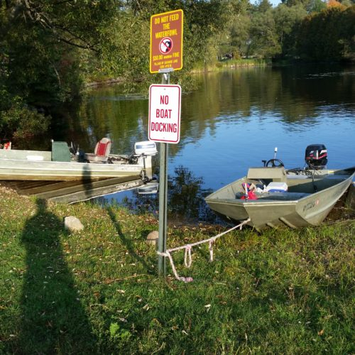 "A boat is tethered to the post of a sign that reads ""No boat docking"" Tuesday evening on Saranac Lake's Lake Flower, at the Ice Palace site next to the state boat launch. (Photo provided — Bob Sweet)"