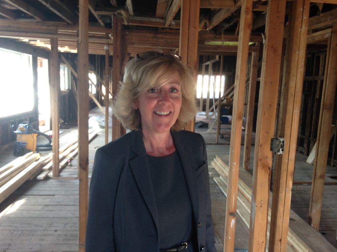 Calli Shelton smiles inside the upper story of the gutted former Dew Drop Inn building last Thursday, Sept. 14. (Enterprise photo — Peter Crowley)