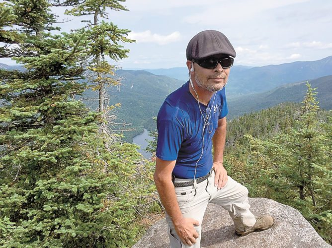 Skip Baker stands atop an unknown mountaintop. (Provided photo — Justin Baker)