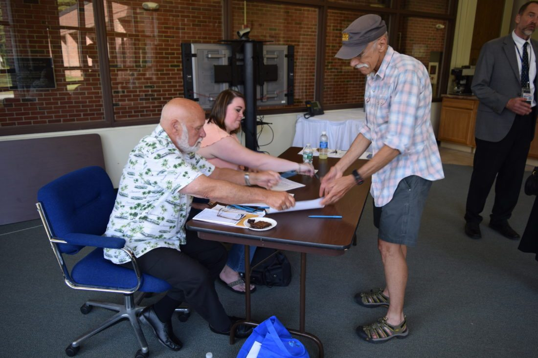 "David Filsinger, right, gets ready to cast his vote for the BOCES capital project Thursday at the Adirondack Educational Center in Saranac Lake. ""I'm all about BOCES. They're going to fix my electric car some day,"" Filsinger said.  (Enterprise photo — Glynis Hart)"