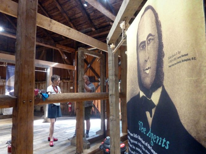 """Martha Swan, executive director of John Brown Lives, takes part in hanging 16 double-sided banners for the """"Dreaming of Timbuctoo"""" exhibit in the barn at 19th-century abolitionist John Brown's homestead in Lake Placid in July 2016. (Enterprise photo — Antonio Olivero)"""
