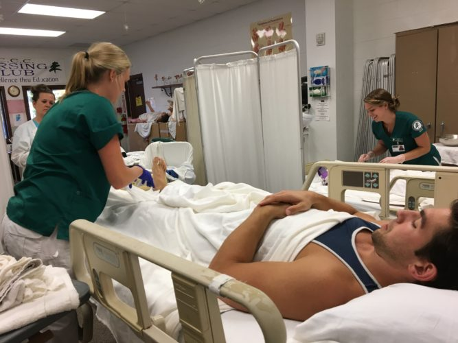 North Country Community College nursing student Matthew Andrews plays the part of a patient for fellow student Aubrey MacIntosh during a lesson on bed bath instruction Thursday on the college's Saranac Lake campus. (Photo provided by North Country Community College)