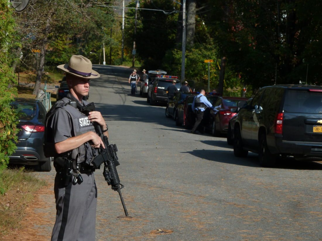 A state trooper with a rifle stands on Saranac Lake's Forest Hill Avenue this afternoon as police look to apprehend suspects from an alleged armed robbery in Plattsburgh. (Enterprise photo — Peter Crowley)