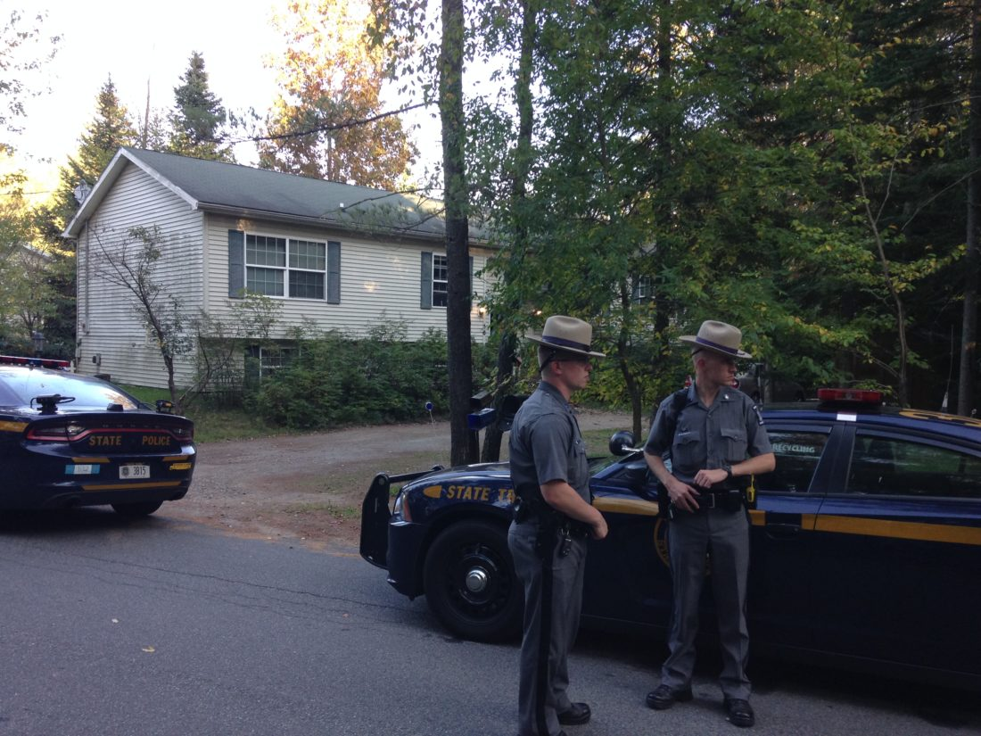 Two state troopers stand guard in front of a house at 16 Rockledge Lane in Saranac Lake, where police believe suspects in a Plattsburgh armed robbery were Saturday. (Enterprise photo — Peter Crowley)