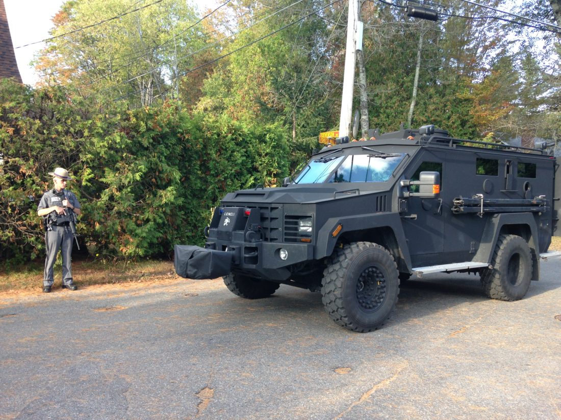 A state trooper with a rifle stands beside an armored Bearcat vehicle of the state police Special Operations Response Team Saturday on Saranac Lake's Forest Hill Avenue. The SORT was pulling out of the neighborhood after an armed robbery suspect was apprehended. (Enterprise photo — Peter Crowley)