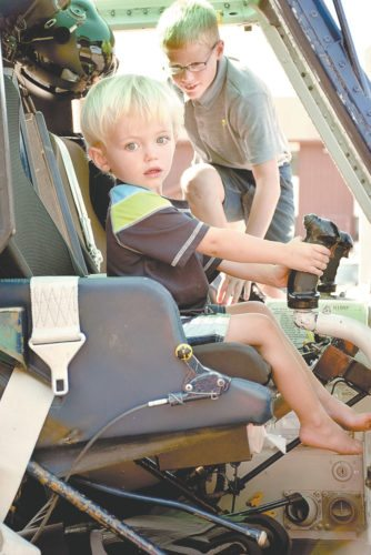 Caed Bowden, 2, of Saranac Lake, sits in the pilot's seat of the New York State Police Aviation Unit helicopter during the agency's 100th anniversary celebration in Ray Brook on Saturday. (Enterprise photo — Justin A. Levine)