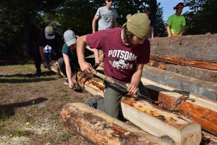 North Country Community College student Paige Hart, center, and Mike Gaulin, rear, and Tim Otis, both of Paul Smith's College, peel bark off a log that will become part of a new lean-to at the NCCC Saranac Lake campus.  The lean-to is part of an outdoor classroom  project between the two schools, and included the installation of benches last year. Students and professors from both colleges were working on the lean-to, behind Hodson Hall, on Saturday. (Enterprise photo — Justin A. Levine)