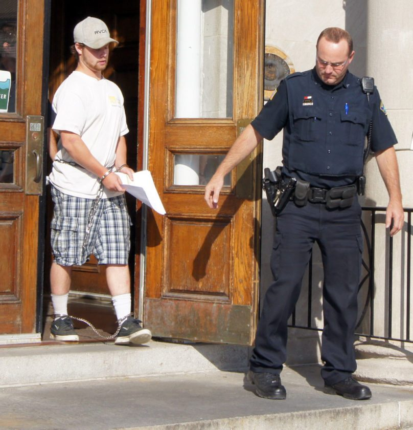 Seth Pickreign, suspecting of dealing drugs, is escorted from the Harrietstown Town Hall with Saranac Lake police Patrolman Leigh Wenske after being arraigned in town court. (Photo provided by Saranac Lake Police Department)