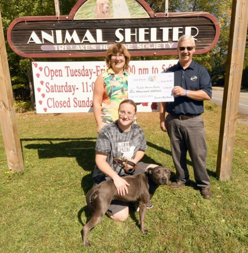 Tri-Lakes Humane Society manager Lena Bombard holds onto Chula while High Peaks Distributing manager Bob Dillon presents the shelter's treasurer Leah Bedore with a $6,000 check that was raised during the 39th annual Bar Fly Open golf tournament held at the Lake Placid Resort's Links Course earlier this month. (Enterprise photo — Lou Reuter)