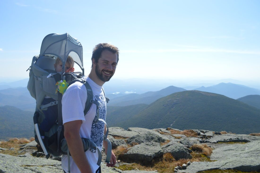 Weston enjoys the shade on his dad Dave's shoulders as they take in the view of the High Peaks Wilderness Saturday afternoon from Mount Marcy, New York state's highest point. (Enterprise photo —Antonio Olivero)