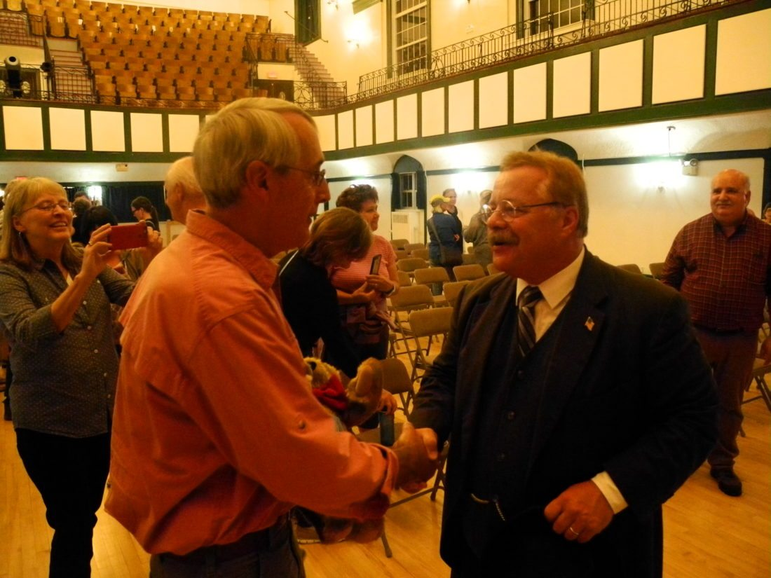 Roger Gorham of Rainbow Lake shakes hands with Theodore Roosevelt impersonator Joe Weigand after  winning a teddy bear donated  by the Vermont Teddy Bear Company in a contest at Wiegand's free performance Sept. 19 at the Harrietstown Town Hall in Saranac Lake. (Enterprise photo — Aaron Cerbone)
