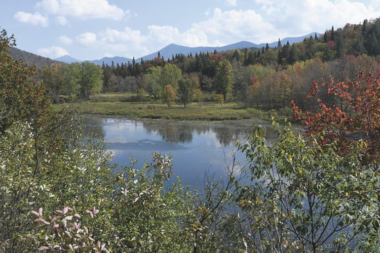 From the left, Whiteface, Moose and McKenzie mountains provide an autumn backdrop as the Saranac River winds along state Route 3 between Saranac Lake and Bloomingdale. (Enterprise photo — Lou Reuter)