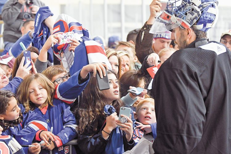 New York Rangers goaltender Henrik Lundqvist greets fans looking for autographs following Monday's team practice at the Olympic Center's USA Rink. The Rangers worked out before a packed rink of 500 fans as they prepare to open the NHL regular season on Thursday. (Enterprise photo — Lou Reuter)