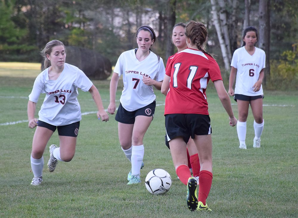 Tupper Lake's Loran Kavanagh (13) and Emma St. Pierre (7) descend on Brushton-Moira sophomore Abby Trimm during the first half of Tuesday afternoon's game in Tupper Lake. (Enterprise photo — Justin A. Levine)