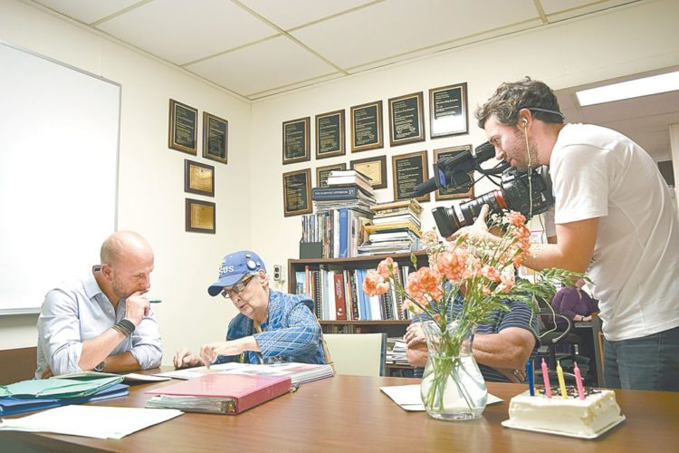 Probate researcher Brice Routier, left, shares documents with Shirley Hosler, who turned 81 Tuesday, while a cameraman from TVF1 films the proceedings at the Adirondack Daily Enterprise. (Enterprise photo — Glynis Hart)