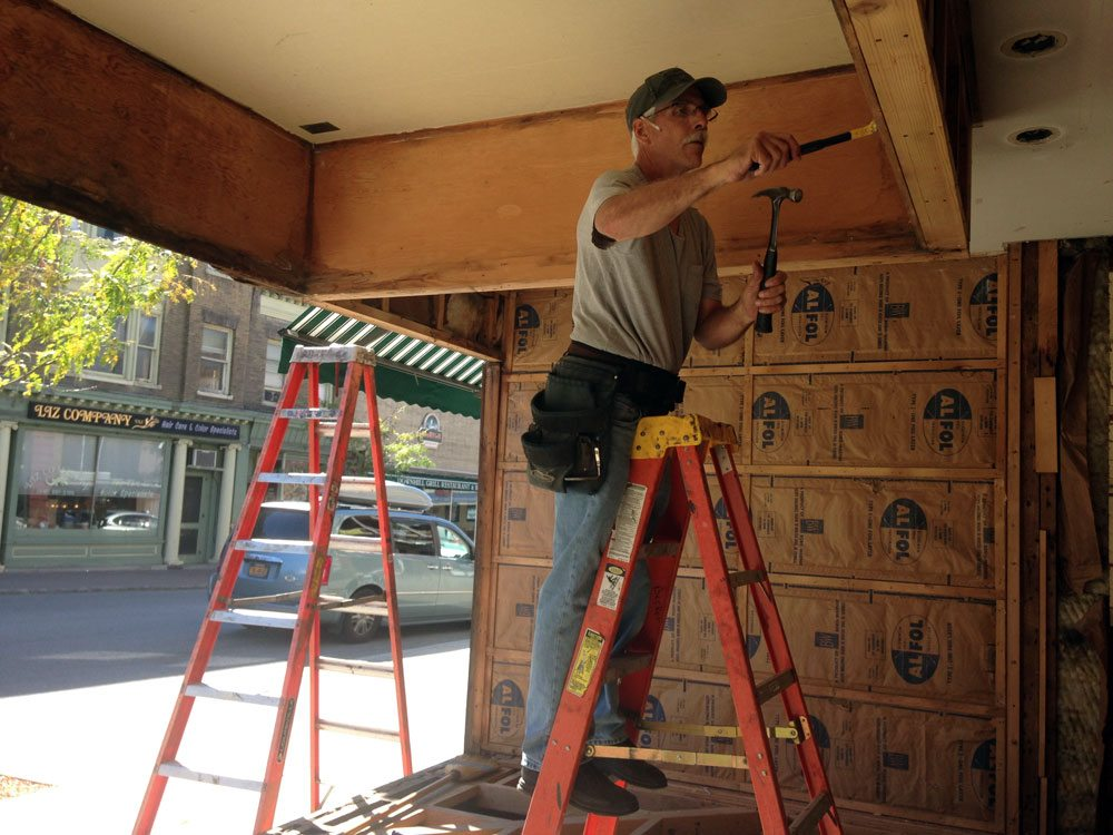 Ray Shumway of R&C Becker Construction of Tupper Lake takes apart the facade of Blue Line Sports on Main Street in downtown Saranac Lake Tuesday. The storefront is being renovated with some help from a state Main Street grant that is also helping fund upgrades to five other downtown buildings. (Enterprise photo — Peter Crowley)