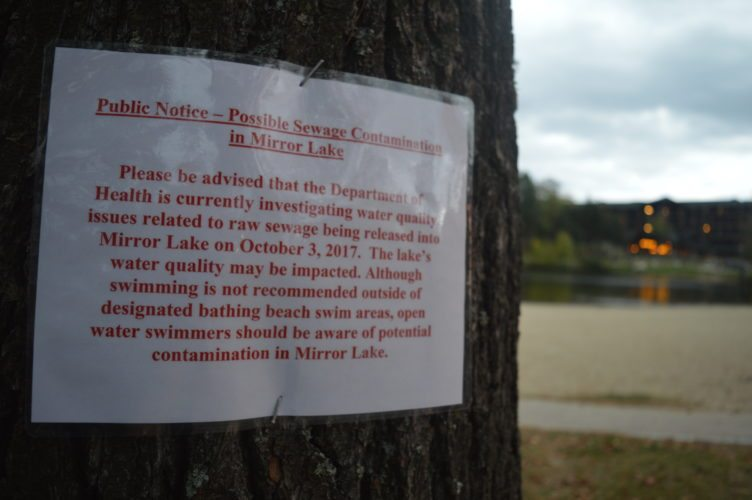 A sign posted at the Lake Placid village beach Wednesday informs people of a sewer leak and asks them to avoid swimming in the water. (Enterprise photo — Antonio Olivero)