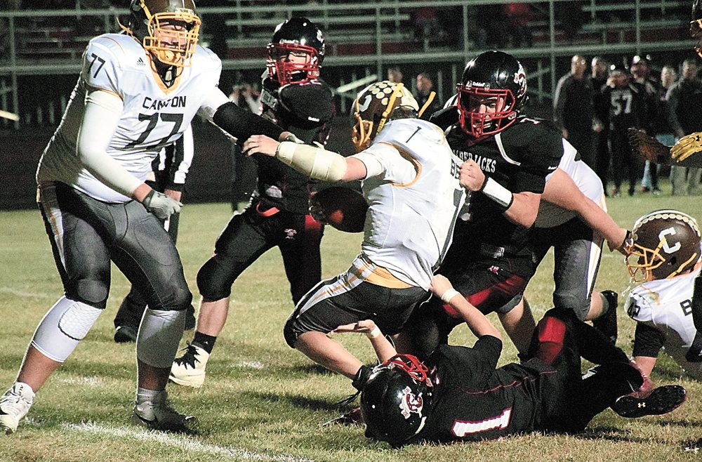 Tupper Lake players Brennen McComber and Cody Pioli (31) take down Canton running back Robert Beaudin during the fourth quarter of Friday night's game in Tupper Lake. (Enterprise photo — Justin A. Levine)