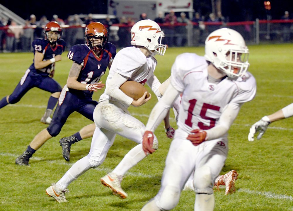 Saranac Lake quarterback DJ Morgan picks up yards on running play while teammate Ward Walton turns upfield looking to block a defender. (Enterprise photo — Lou Reuter)