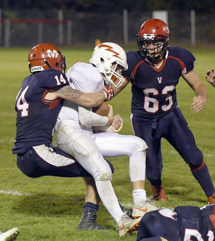 Red Storm senior Emery Swanson is tackled by Moriah's Ryan Flack after a short pass reception in the first half of Friday's game. Also pictured is Vikings' defender Jacob Gibeau. (Enterprise photo — Lou Reuter)