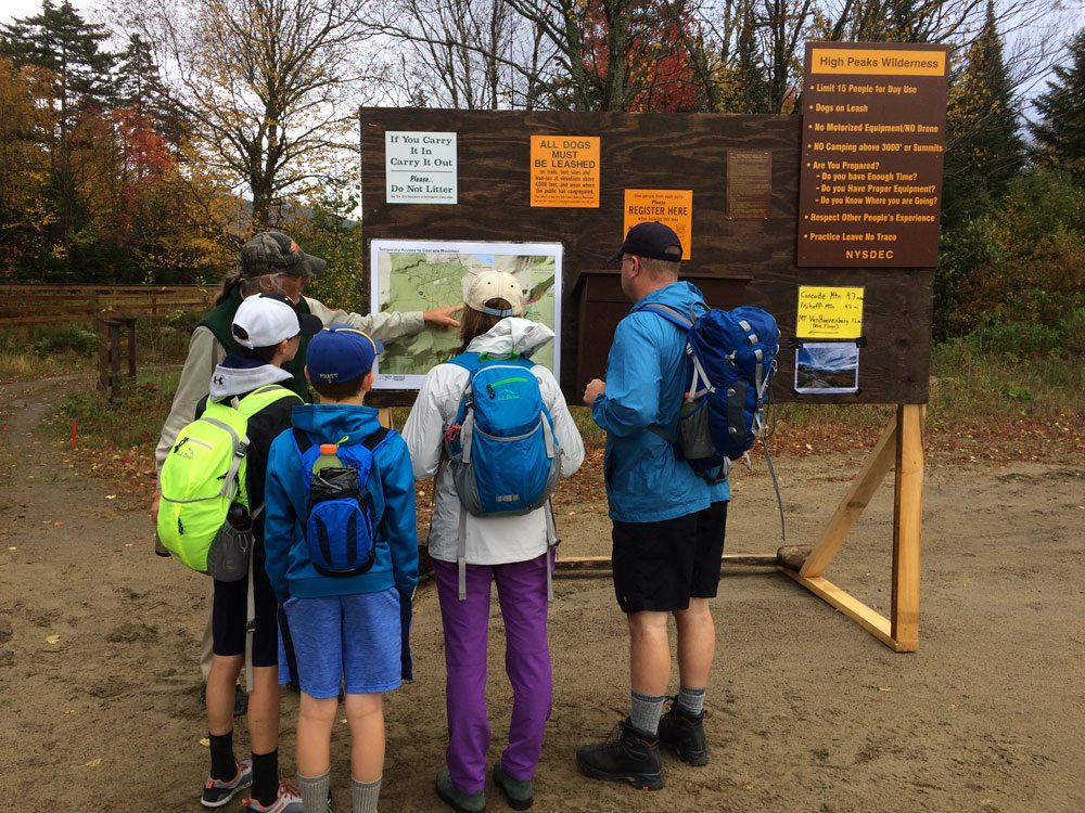 Ron Konowitz, a trailhead steward with the Adirondack 46ers organization, shows a family of hikers a map of the rerouted Cascade Mountain trail on Sunday morning. The state temporarily rerouted the trail for the busy Columbus Day and Canadian Thanksgiving weekend. (Enterprise photo — Justin A. Levine)