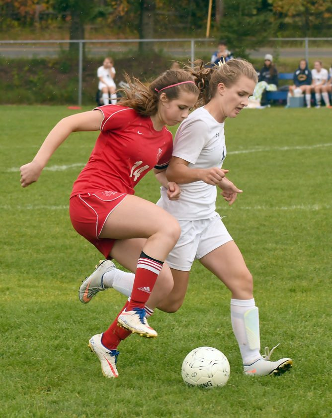 Saranac Lake's Grace Clark, left, and Camille Craig of Lake Placid battle for the ball in close quarters during Saturday's match on the Blue Bombers' field. The contest was originally slated to be an official game but ended up as a scrimmage because the referees did not show up. (Enterprise photo — Lou Reuter)