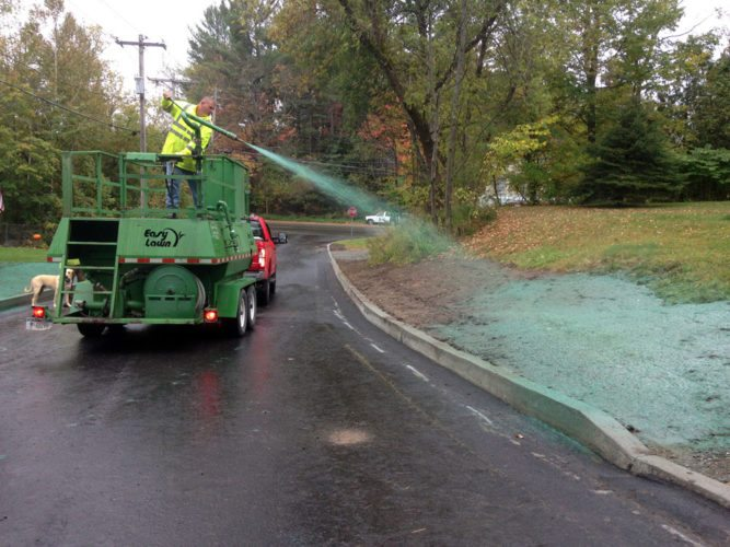 """Chris Blanchard of the village of Saranac Lake's Department of Public Works uses a """"hydroseeding"""" machine, borrowed from Essex County, Friday on Keene Street to spray a mix of grass seed, mulch and fertilizer — dyed bright green — on people's yards beside where the village reconstructed the road and put in curbs. (Enterprise photo — Peter Crowley)"""