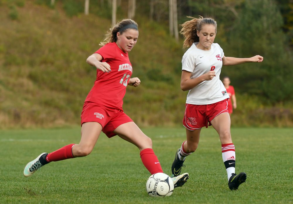 Beekmantown's Kristen Villemaire gets set to kick the ball while Saranac Lake's Jillian Duffy closes in to defend during the first half of Tuesday's match at Schroeter's Field in Saranac Lake. (Enterprise photo — Lou Reuter)