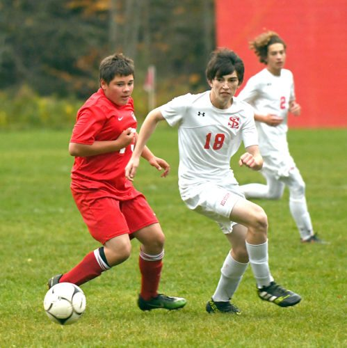 Saranac Lake's Daniel Foley, right, spins past a Beekmantown opponent while pursing the ball during Wednesday's match at Schroeter's Field. Also pictured in the background for the Red Storm is Griffin Pelish. (Enterprise photo — Lou Reuter)