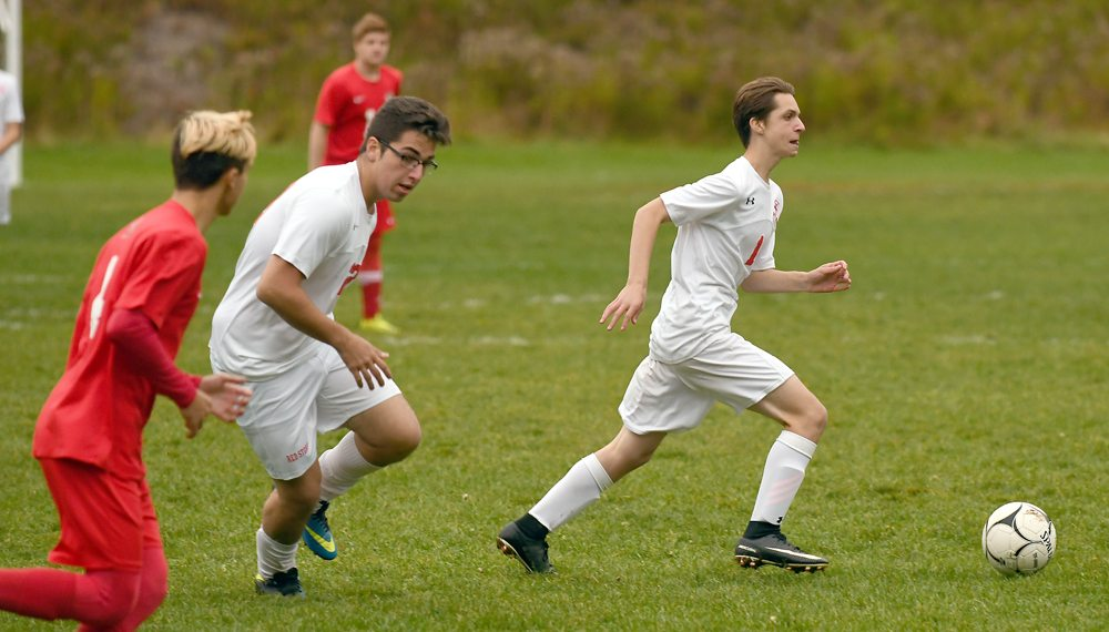 Christian Monty of Saranac Lake advances the ball while teammate Victtor Moraes stays close to the play during the opening half of Wednesday's match. (Enterprise photo — Lou Reuter)