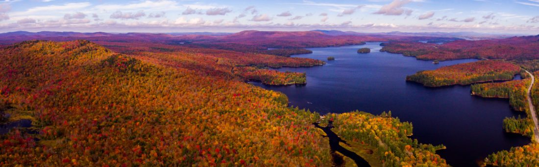 Reds, oranges and yellows top the trees looking up the lake from Bog River outside Tupper Lake this week. State Route 30 is seen at far right and Bog River Falls is seen lower center with Tupper Lake in the distance at the top right. (Photo provided — Mitch Harriman)