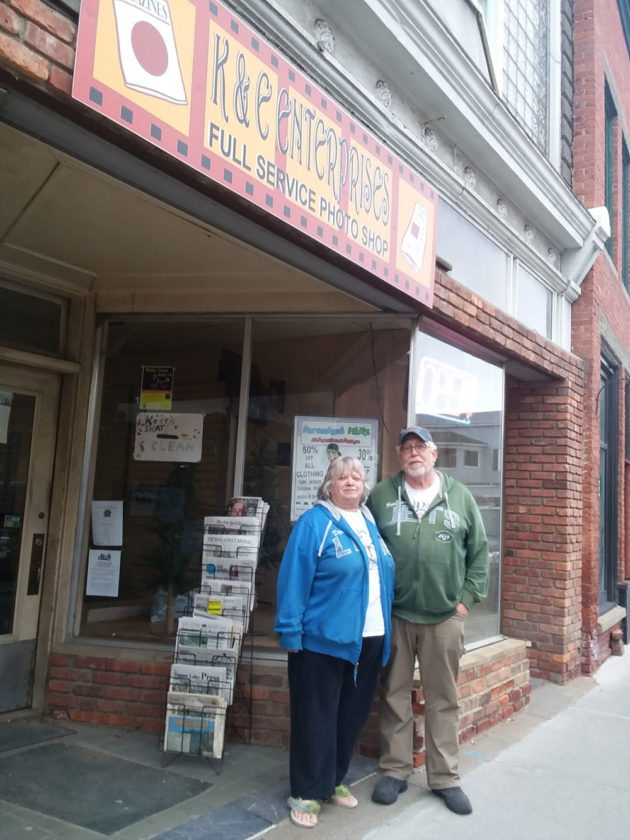 Karen and Chris Harrington stand in front of the store at 38 Broadway where they've worked for two decades. Recently, they sold the building to a restaurateur from Plattsburgh.  (Enterprise photo — Glynis Hart)