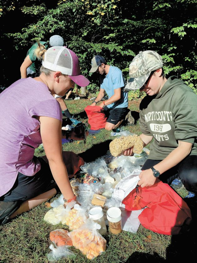North Country Community College wilderness recreation program students Tarah Schlueter of Colorado, left, and Julie Landry of Clifton Park sort through their food supplies at Little Clear Pond during the transition from paddling to backpacking on their 30-day practicum. (Photo provided)