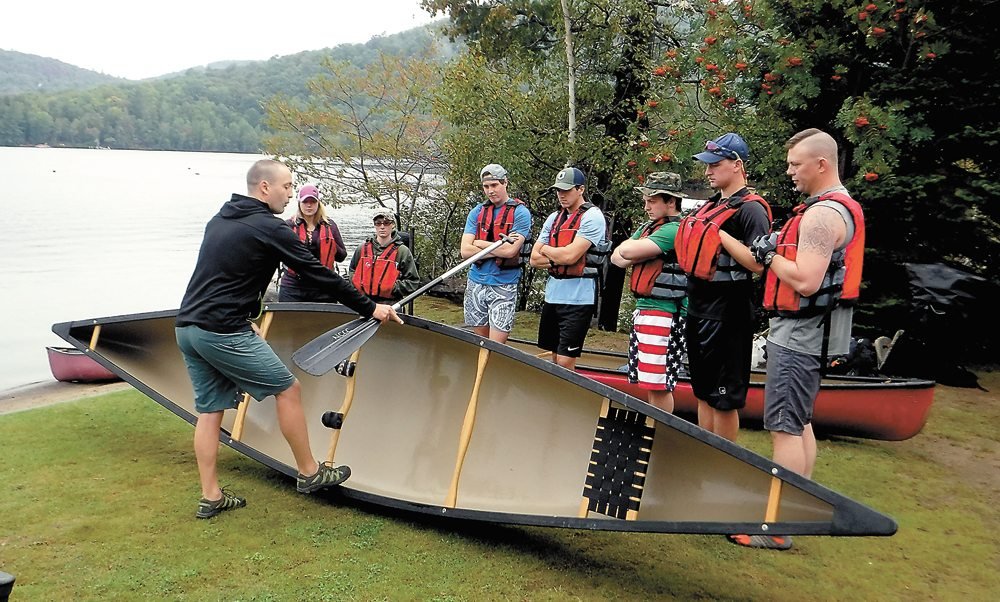 NCCC instructor Tyler Meriam teaches, from left, Tarah Schlueter, Julie Landry, Henry Uzdavinis, Aaron Rosati, Mike Woolheater, Garett Winters and Mike Brewer the anatomy of a tandem canoe in Blue Mountain Lake. (Photo provided)